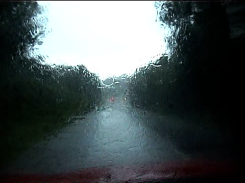 Track forward from inside of car as rain beats down heavily on windscreen during floods Boscastle Cornwall 2004