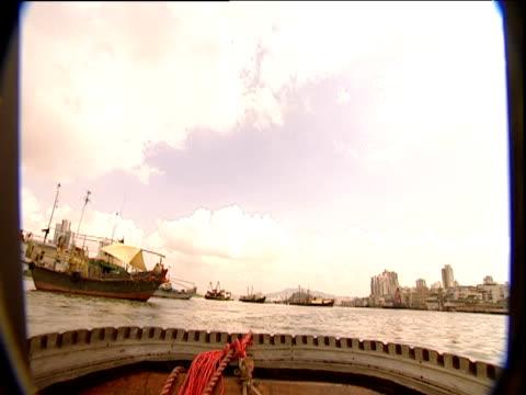 vídeos de stock e filmes b-roll de track forward from small boat across harbour as passenger ferry passes hong kong - embarcação comercial