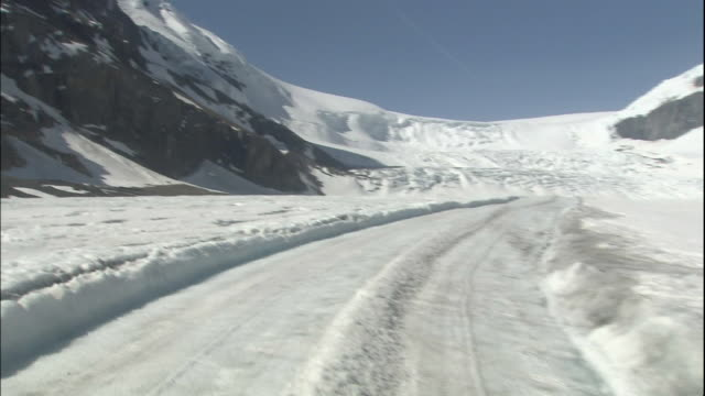 vidéos et rushes de track forward from snow bus front windscreen as driving up athabasca glacier, canadian rocky mountains park, canada - pare brise