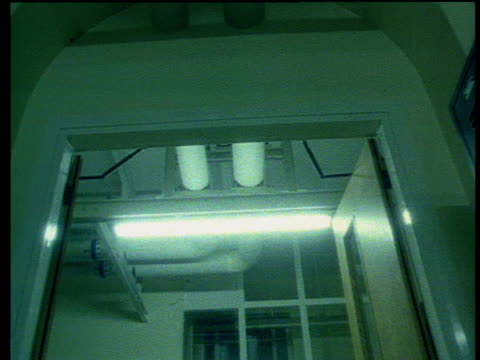 Track forward from the perspective of a patient being wheeled down hospital corridor on trolley looking toward the ceiling.