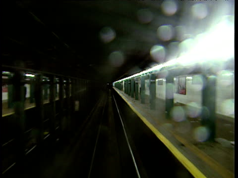 Track forward from train as it arrives at metro platform New York