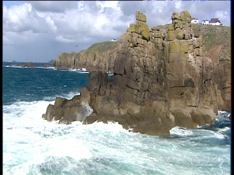 track forward low over armed knight rocks to land's end cliffs and hotel on cliff top cornwall - 石灰岩点の映像素材/bロール