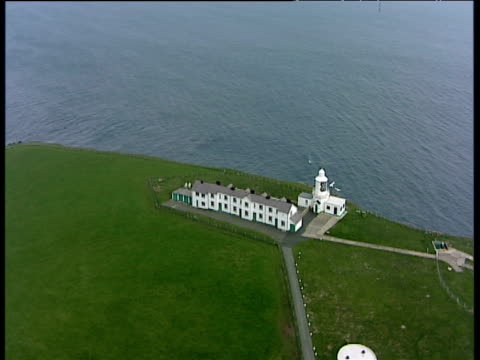 vídeos de stock, filmes e b-roll de track forward over and around lighthouse buildings and heli-pad at west blockhouse point st anne's head peninsular milford haven - helicopter landing pads