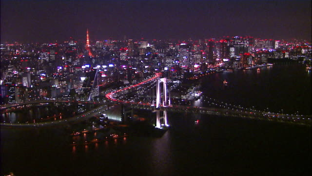 Track forward over Bay Bridge and high rise city buildings with Tokyo Tower in distance