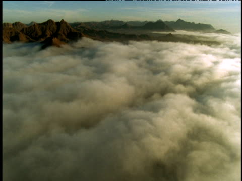 Track forward over cloud towards mountain range, Namibia