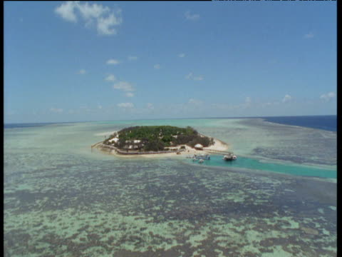 track forward over coral reef as helicopter approaches and lands on heron island - helicopter landing pads stock videos and b-roll footage