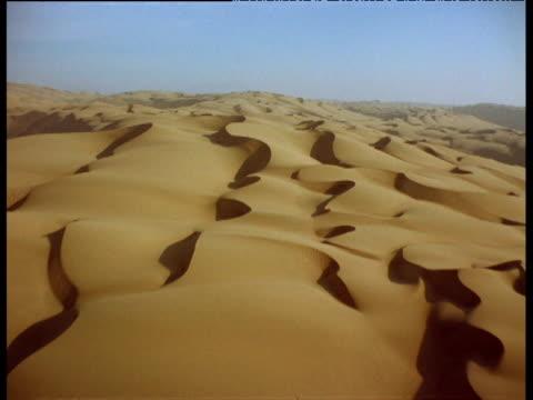 Track forward over curving dunes across desert landscape
