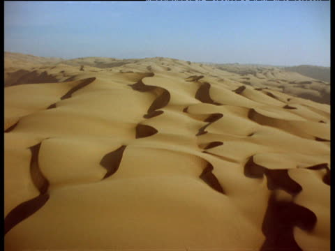 track forward over curving dunes across desert landscape - sahara desert stock videos & royalty-free footage
