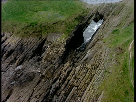 track forward over devil's bridge (natural blow hole) in worm's head gower peninsula south wales - galles video stock e b–roll