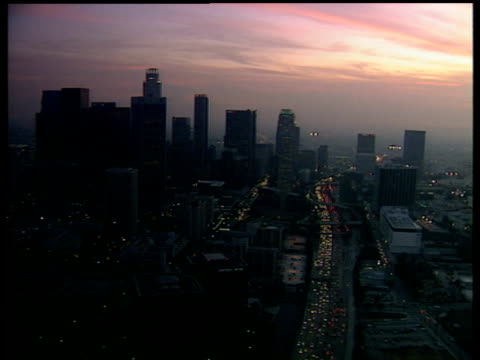 Track forward over downtown Los Angeles and dark orange dusky sky camera follows traffic along motorway between skyscrapers and other tall buildings