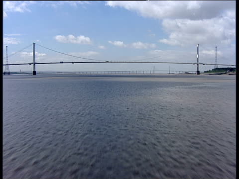 track forward over estuary towards severn bridge and severn second crossing (new severn bridge) in distance - river severn stock videos & royalty-free footage