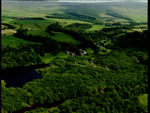 track forward over lush green countryside with scattered farms and large stately home pennines - pennines stock videos and b-roll footage