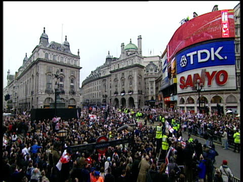 vídeos de stock, filmes e b-roll de track forward over massive crowd congregated in piccadilly circus to 'sweet chariot' bus seen in distance england rugby union world cup victory... - estilo dos anos 2000