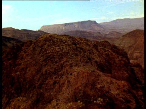 vídeos y material grabado en eventos de stock de track forward over mountain top to reveal colorado river and hoover dam - desigual con textura