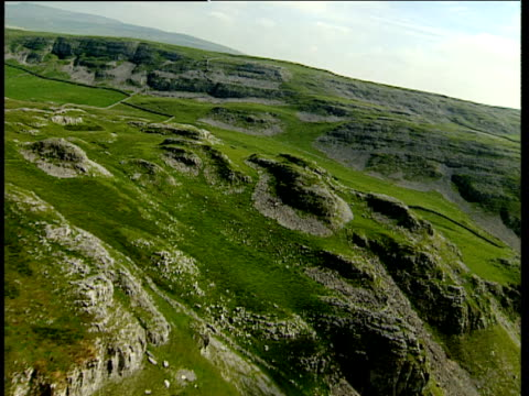 vidéos et rushes de track forward over peaks of limestone hills with dry stone walls and sheep grazing pennines - outcrop