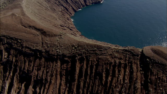 track forward over remains of volcanic crater to sea isabela galapagos islands available in hd. - galapagos islands stock videos & royalty-free footage