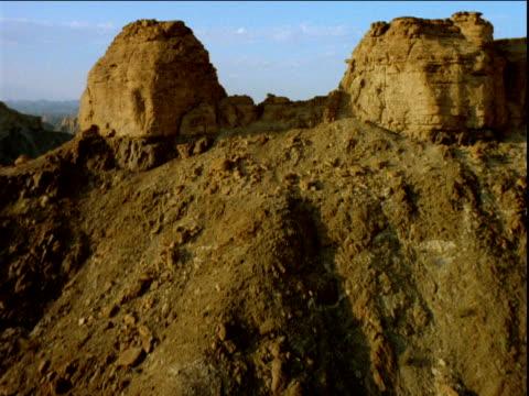 track forward over rock formation on mountain top towards mountain range beyond - ムラがある点の映像素材/bロール