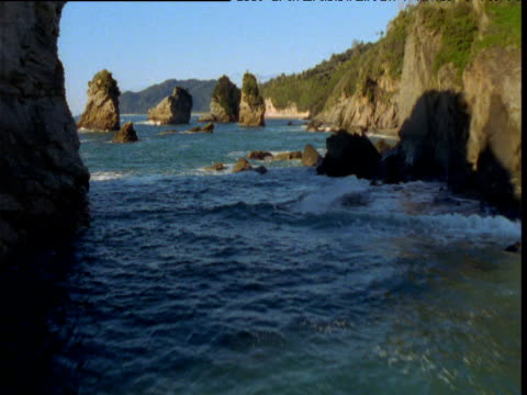 track forward over surf and rocky coastline, otago, south island, new zealand - otago region stock videos & royalty-free footage