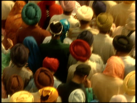 Track forward over top of densely packed crowd men in turbans and women in head scarves facing away from camera