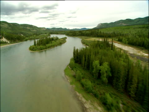 Track forward over turquoise Yukon river fir trees and islets