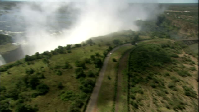 track forward over victoria falls, zimbabwe, aerial shot - victoria falls stock videos and b-roll footage