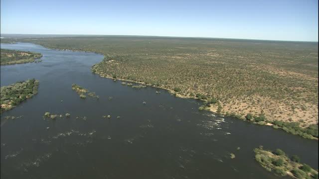 Track forward over Zambezi, Victoria Falls in distance, Zimbabwe, Aerial Shot