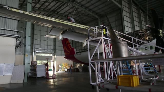 track forward past a boeing co 7378gj aircraft sitting next to a bombardier inc q400 nextgen passenger aircraft at the air works engineering pvt... - 航空宇宙産業点の映像素材/bロール