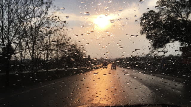 Track forward through car's windshield with raindrops during sunset