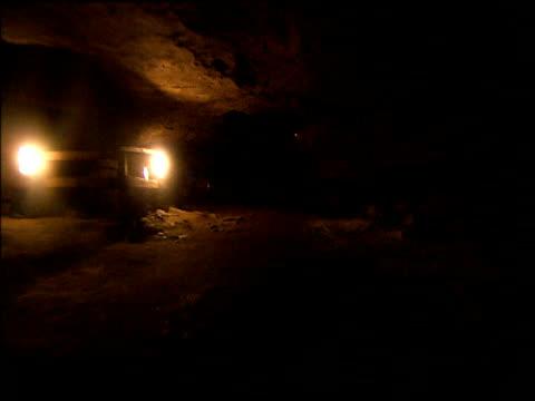 track forward through dark underground passage lit with lanterns in peak cavern castleton derbyshire - derbyshire stock-videos und b-roll-filmmaterial