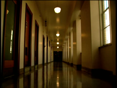 track forward through hospital corridor lined with doorways on one side and windows on the other, doors to operating theater at end - korridor stock-videos und b-roll-filmmaterial