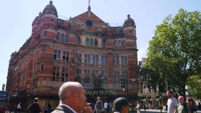 Track forward through pedestrians crossing the road towards the Palace Theatre showing Harry Potter and the Cursed Child