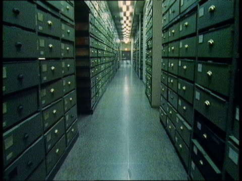 track forward through small aisle in between towering green filing cabinets - bbc archive stock-videos und b-roll-filmmaterial