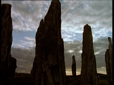 Track forward to Callanish stones in silhouette with grey clouds across sky, Outer Hebrides