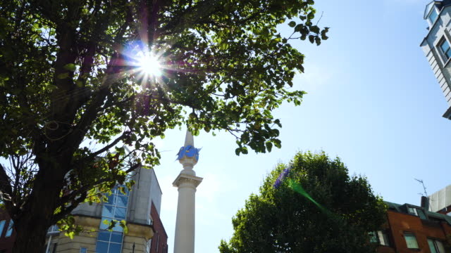 Track forward to the column at Seven Dials as sunlight glitters through the trees