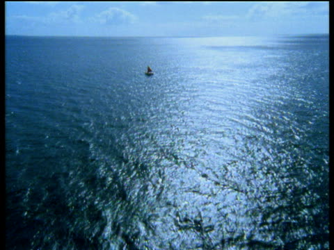vidéos et rushes de track forward toward small sail boat in middle of blue ocean sun reflecting off surface of water marquesas islands - dom tom