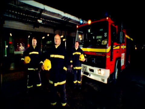 track forward towards three fire fighters standing next to fire engine with flashing lights england - fire station stock videos & royalty-free footage
