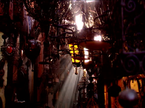 vídeos de stock e filmes b-roll de track forward under glass and metal lamps hanging in souk sun rays shine through - banca de mercado