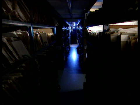 Track forwards down narrow corridor of storeroom files and boxes on shelves either side moody blue lighting