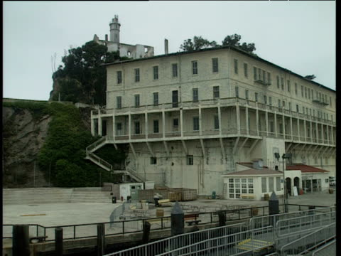 Track forwards from boat along side Alcatraz Island. Exterior of prison with windows and balconies