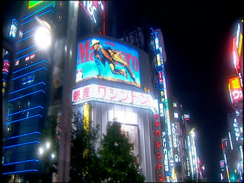 track forwards from car along tokyo streets at night neon signs and billboards flashing on high rise buildings - 1998 stock videos and b-roll footage