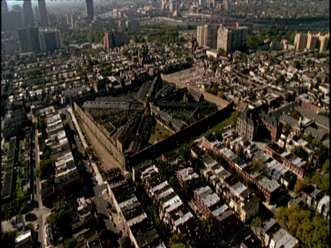 track forwards from helicopter over built up outskirts of philadelphia eastern state penitentiary (the world's first prison) philadelphia skyscrapers in background. track towards star shaped buildings of prison - eastern state penitentiary stock videos & royalty-free footage