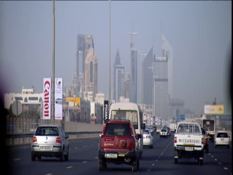 Track forwards in car along busy dual carriageway skyscrapers in distance Dubai