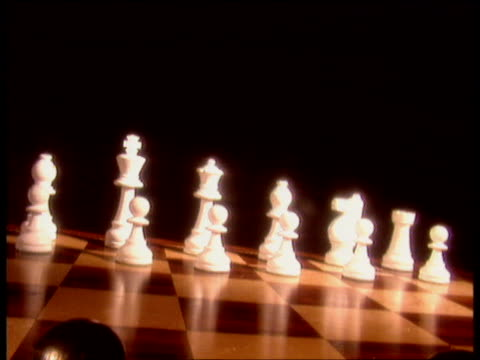 Track forwards over black chess pieces on board towards white pieces