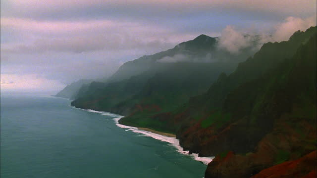 Track forwards over rocky coastline as white clouds drift above, Kauai Available in HD.