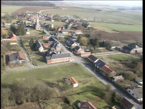 vidéos et rushes de track forwards over small village including church farm houses and fields somme - ferme bâtiment agricole