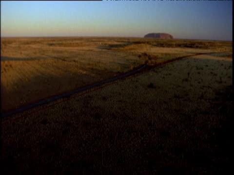 Track forwards slowly towards Uluru on horizon green bush in foreground surrounding country road Australia