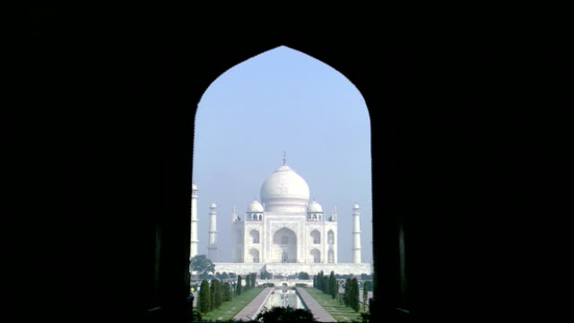 track forwards through archway towards taj mahal, agra - mausoleum stock videos and b-roll footage
