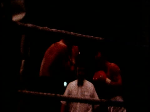 track forwards towards boxing ring with red gloved boxers, referee watching over fight - 格闘技リング点の映像素材/bロール