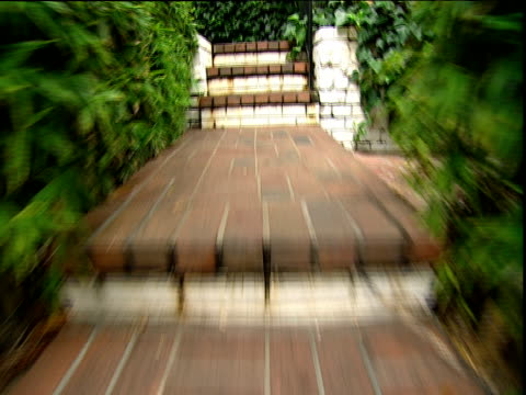 track forwards up stone steps through dense foliage grounds of hotel chateau marmont sunset strip los angeles - 2000s style stock videos & royalty-free footage