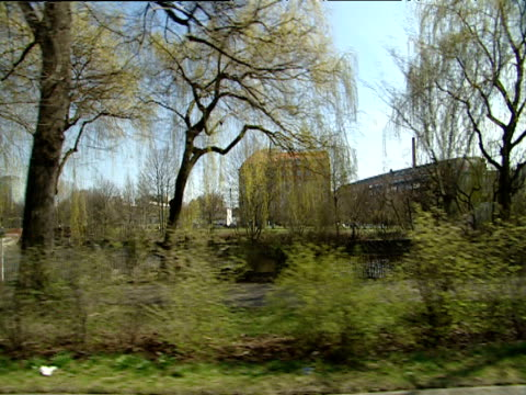 stockvideo's en b-roll-footage met track from car driving through suburban parkland and river area past polizei vans into residential street east berlin - polizei